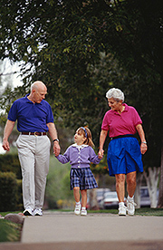 Grandparents and granddaughter (4-5) walking on sidewalk
