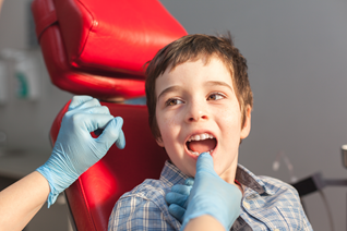 A student has his teeth examined by dentist