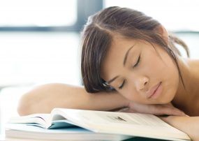 Student sleeping on textbook