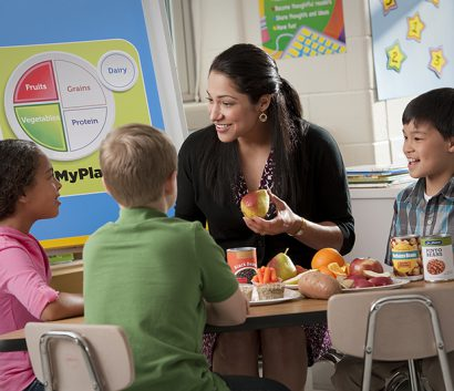 teacher eating healthy lunch with kids