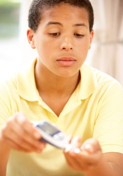 Boy using monitor to check blood sugar level