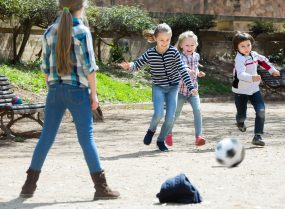 Young kids playing street football outdoors.