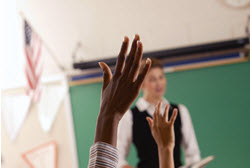 2 students raising their hands to answer the teacher's question in class