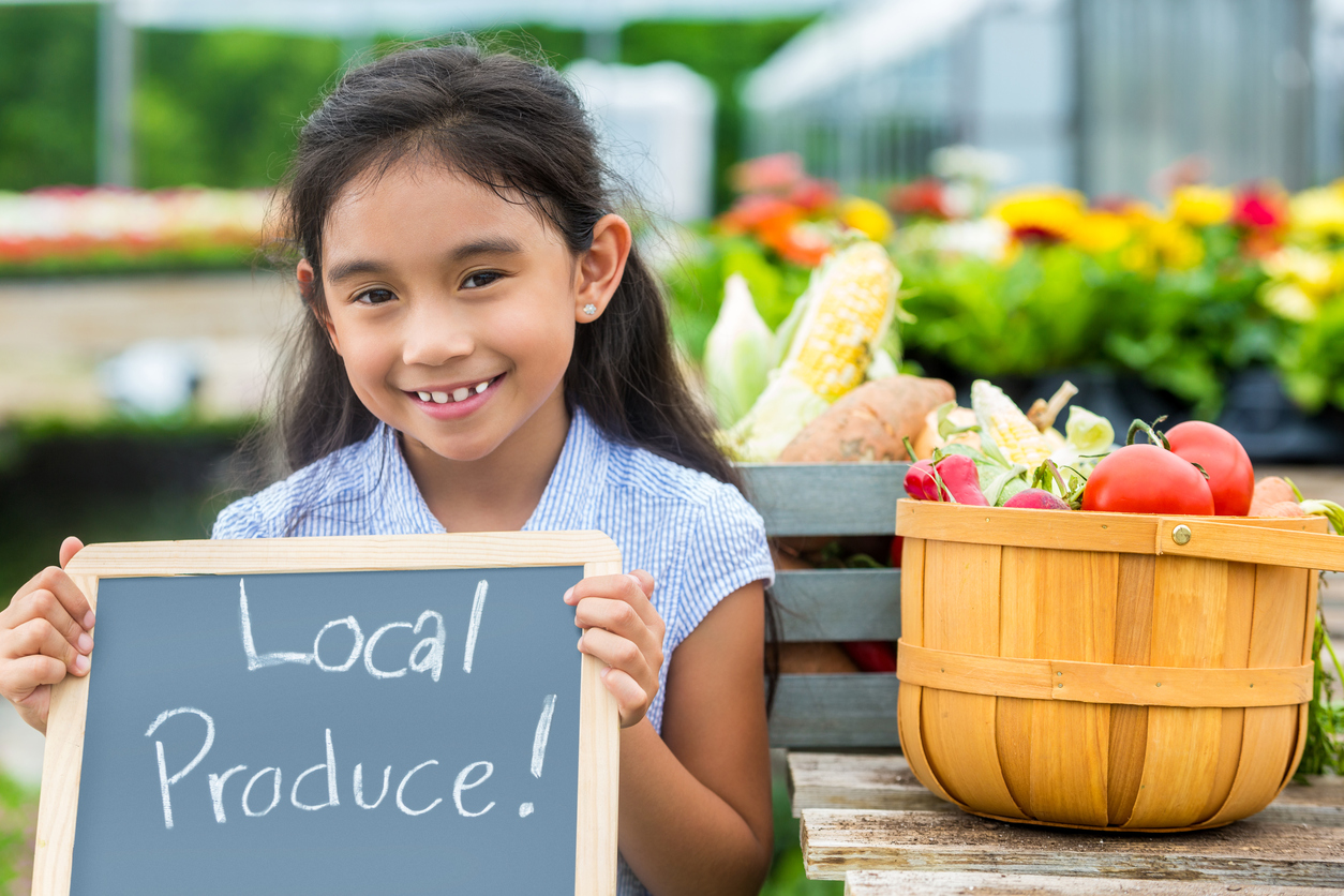 A girl holding a local produce sign