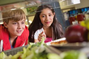 Students choosing healthy or unhealthy food in school lunch line