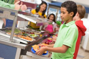 Middle school students getting lunch items in cafeteria line