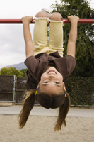 girl hanging on monkey bars