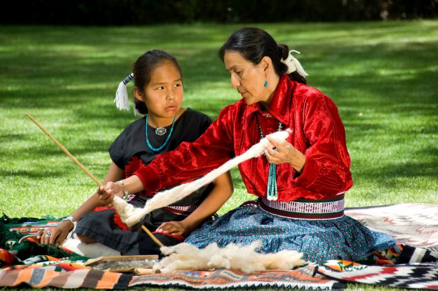 Native American mother demonstrating to daughter how to weave.