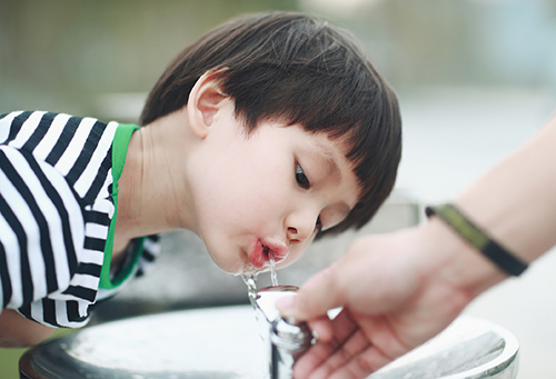 A boy drinking from an outdoor water fountain.
