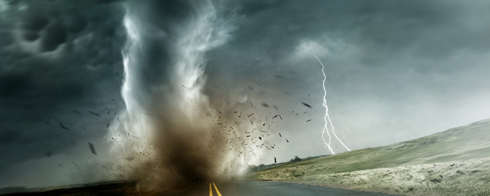 Image of a large tornado during touch down on an empty long road.