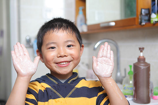 Image of young boy smiling showing his hands with soap