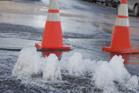 Orange safety cones marking a flooding street