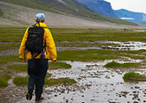 Photo of a hiker walking through a stream in the backcountry, with mountains in the background