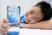 young boy looking at glass of water