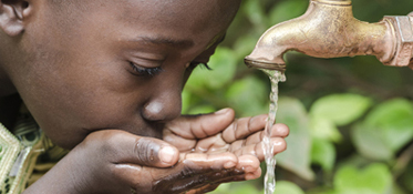 Young boy drinking from a faucet