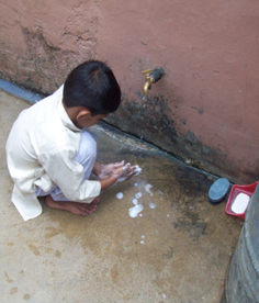 A boy in the developing world washing his hands with soap under an outdoor tap.