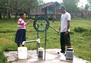 A couple pumps water out of a community well