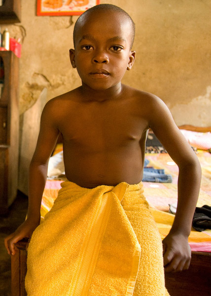 a little boy in the developing world sitting in a clinic awaiting examination