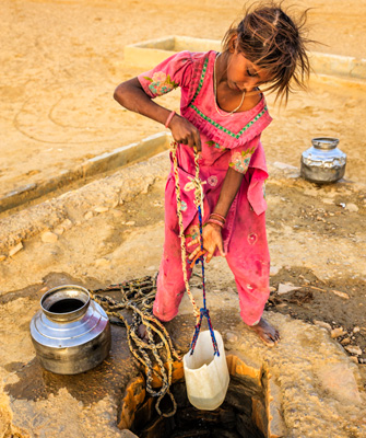 Image of young girl getting water from a well in a plastic container