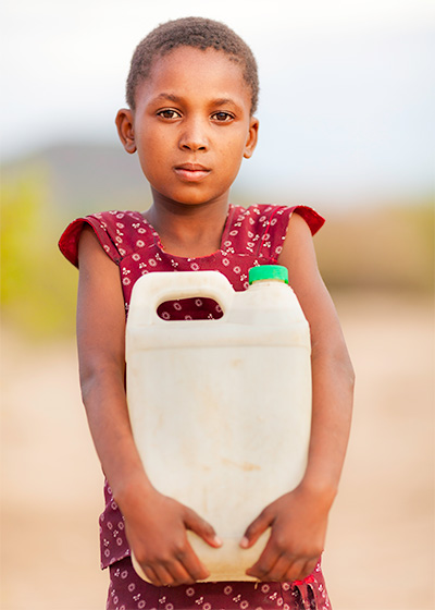 Image of young girl outside holding a jug full of water