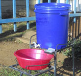 Handwashing station with plastic bucket containing a tap, metal stand, basin for catching water and soap.