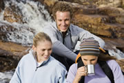 Photo of travelers drinking water from a waterfall