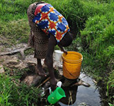 A woman collecting water from a river in Kenya