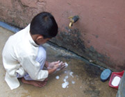 Child washing hands outside under a water spigot