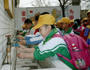 Chinese school children washing their hands at an outdoor washing station.
