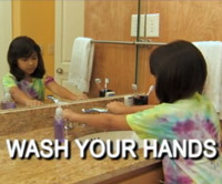 a girl washing her hands with soap at the sink.