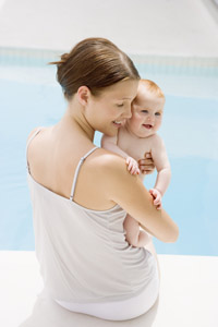 Mother holding baby by the side of the swimming pool