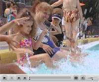 Image excerpt from the video showing a group of women, of various ages, splashing their feet in a pool.