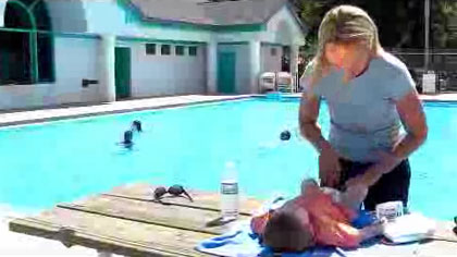 Idaho Dept. of Health and Welfare - Shower before Swimming 3 - Screenshot of a video showing a woman changing a baby's diaper next to the pool