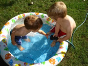 Two boys filling a kiddie pool with water.