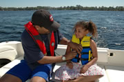 Photo of a father putting a life jacket on his daughter