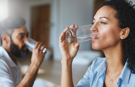woman drinking a glass of water with a man doing the same in the background