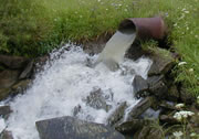 Photo of wastewater coming from a pipe and out into a stream