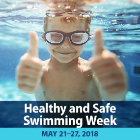 Healthy and Safe Swimming Week is May 21-27, 2018. Photo of a little boy underwater in a swimming pool with goggles giving two thumbs up