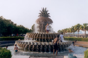 Kids playing in a decorative water fountain.
