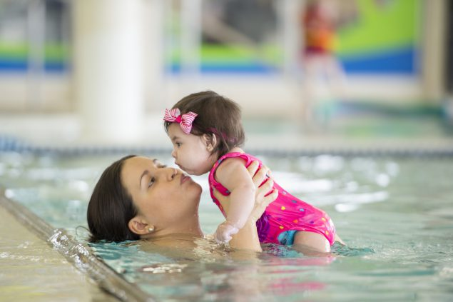 mother giving kisses to a toddler in a swimming pool
