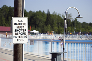 shower next to pool with sign informing swimmers that they must shower before entering pool