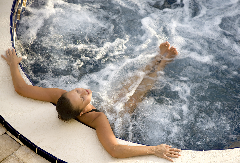 woman relaxing in an outdoor hot tub