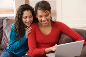African American Daughter and Mother Looking at laptop computer