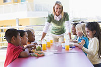 Photo: teacher and kids in school cafeteria