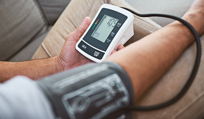 A man using an at-home blood pressure monitor.