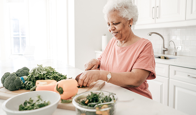 A woman chopping vegetables in the kitchen.