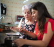 A mother and daughter cooking together in the kitchen.