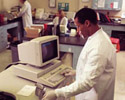 Man in lab coat standing at computer, representing Health Professionals