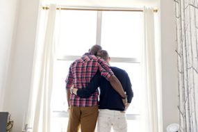 Rear view of gay men standing arms around while looking through window at home