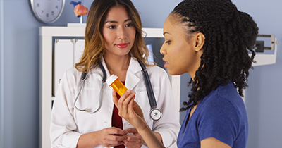 Photo of a patient examining medication with doctor